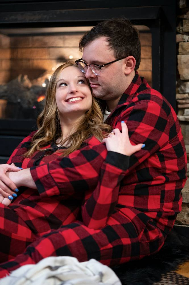 engagement photo in plaid pajamas in front of fireplace