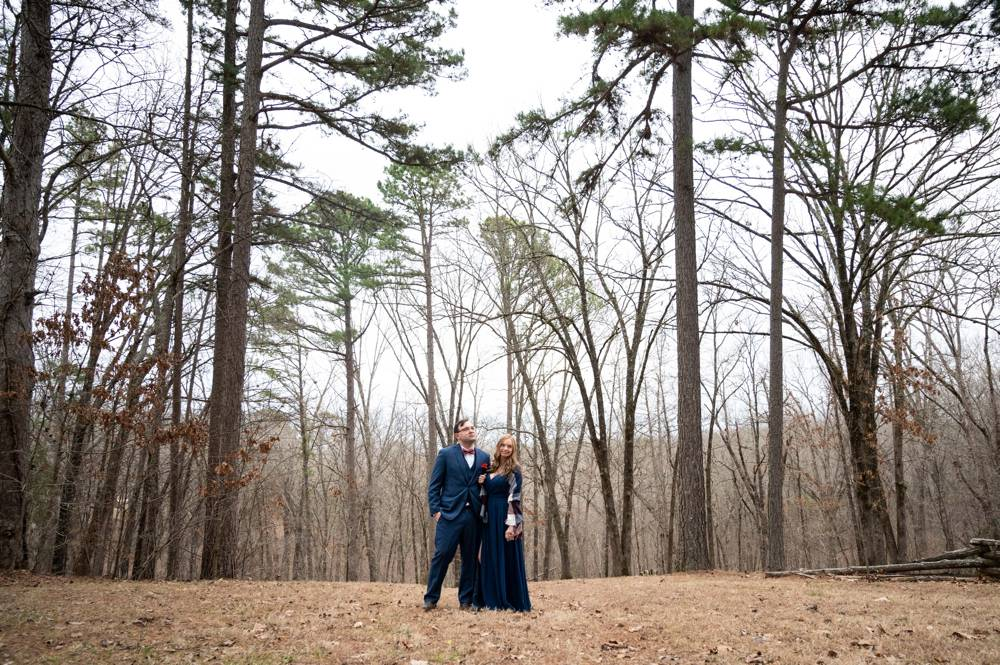 wide shot of engaged couple in woods
