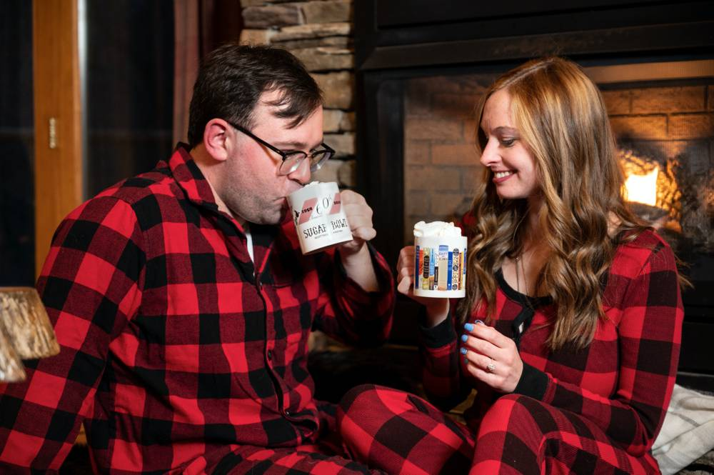 couple in front of fireplace in cabin drinking hot chocolate