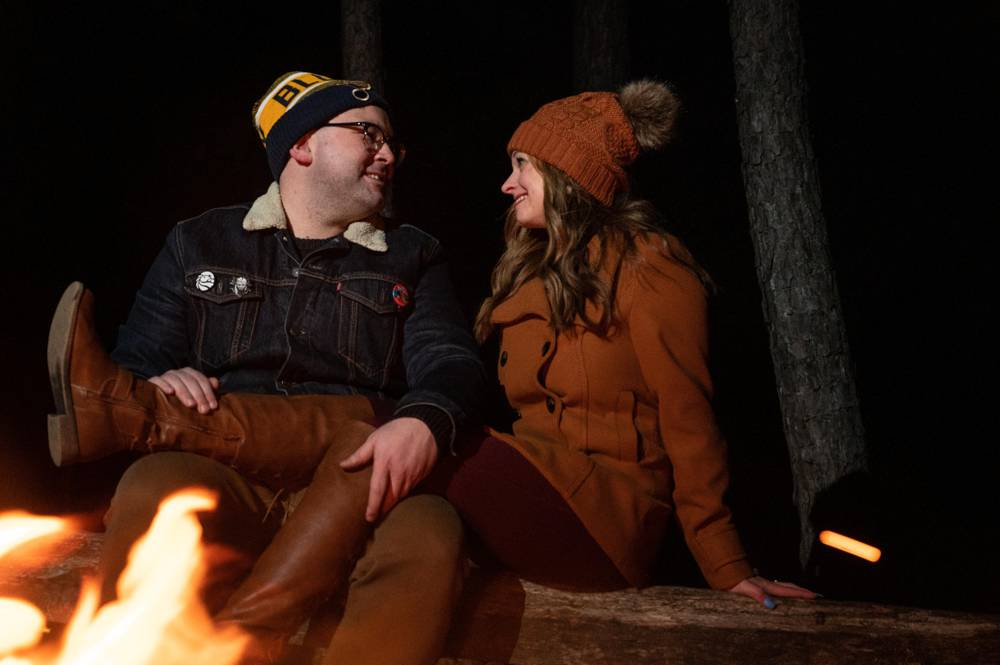 couple sitting on log in front of fire