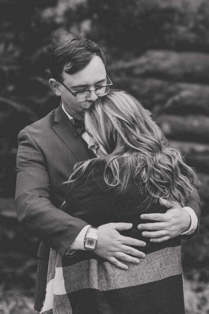 black and white engagement photo kissing her head
