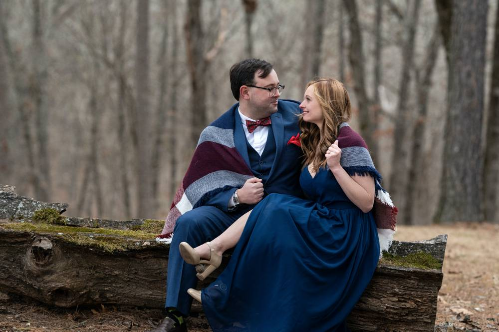 engagement session in the woods sitting on log
