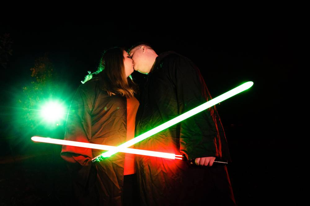 couple kissing and holding light sabers