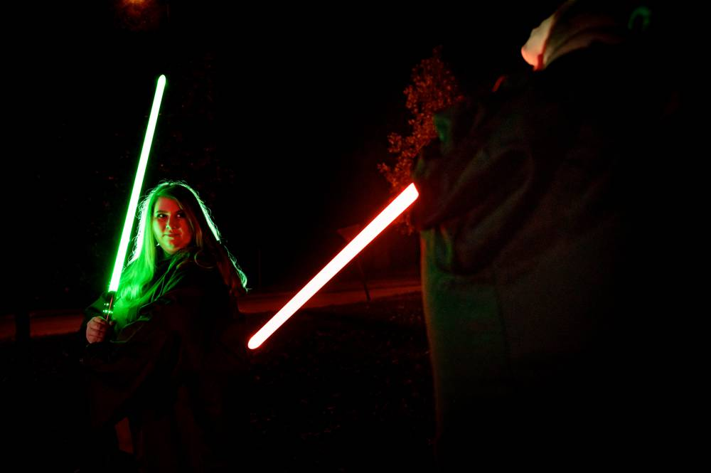 engaged couple posing with Star Wars light sabers