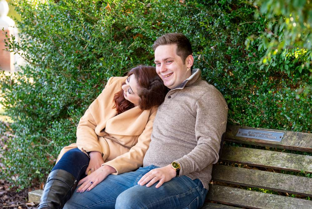 couple laughing and sitting on bench