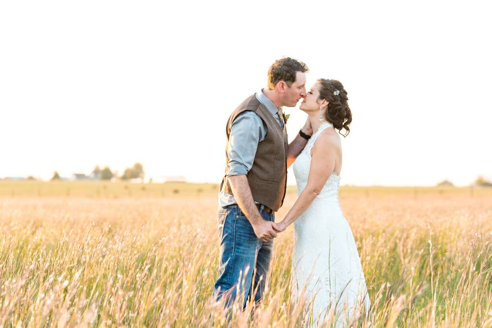 sunlit field with bride and groom