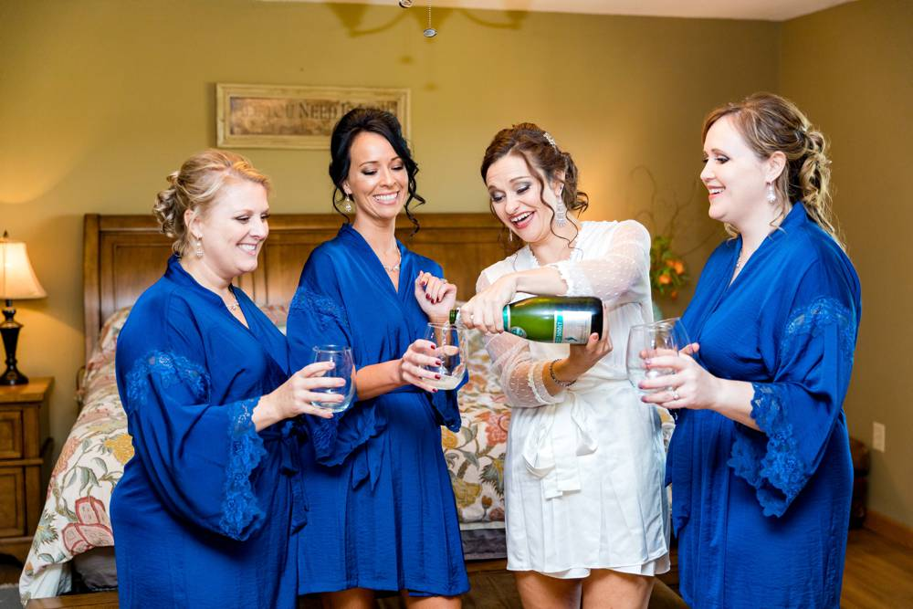 girls in robes pouring champagne