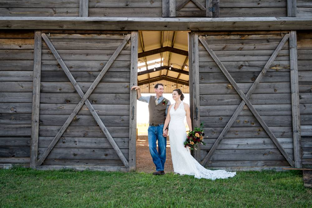 bride and groom in doorway of barn at The lodge at Rock Creek