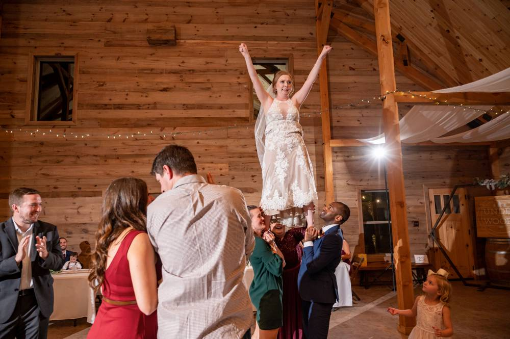 bride being lifted up and doing cheerleader move