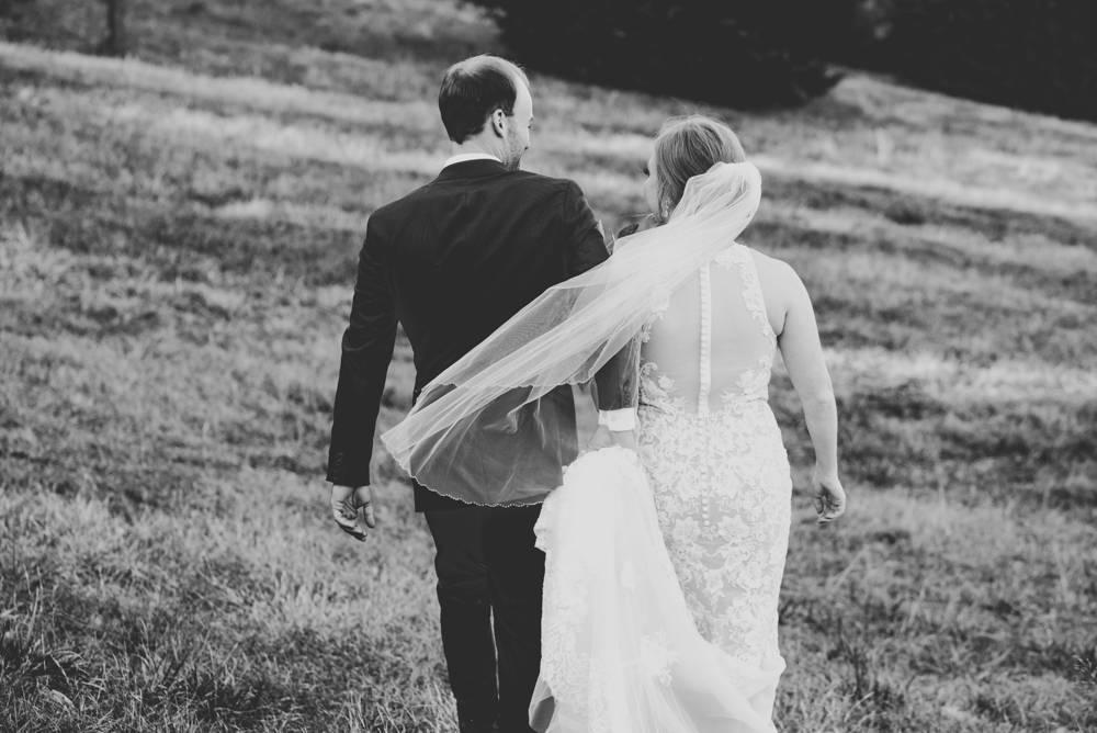 bride and groom walking through a field in black and white