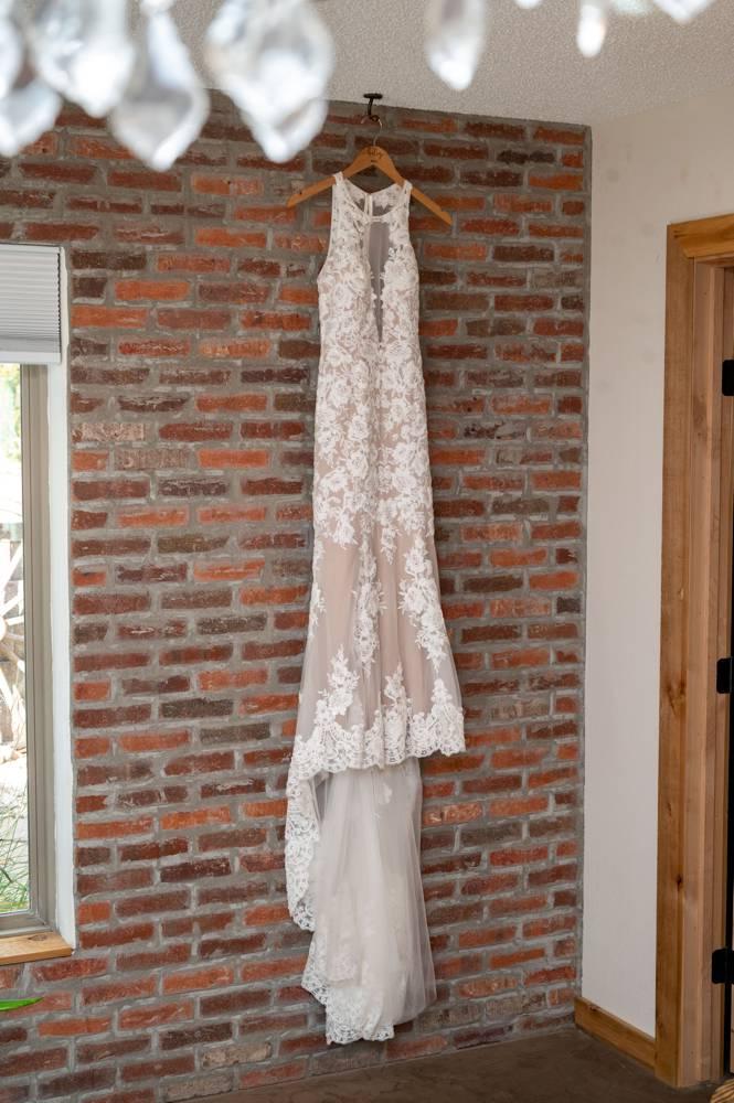 Dress hanging on brick wall