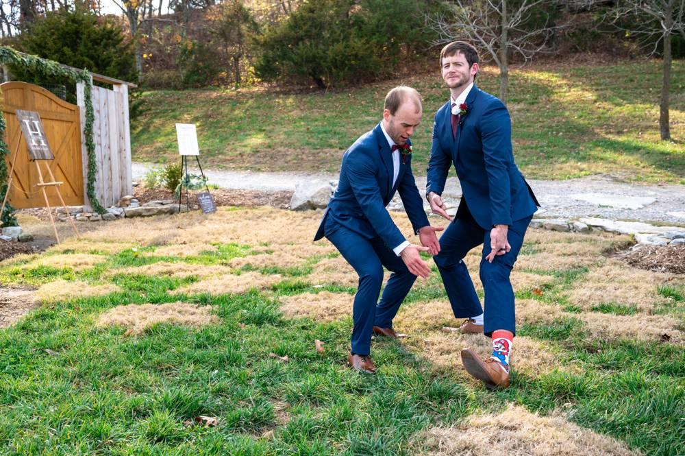 groom goofing off with groomsman showing socks