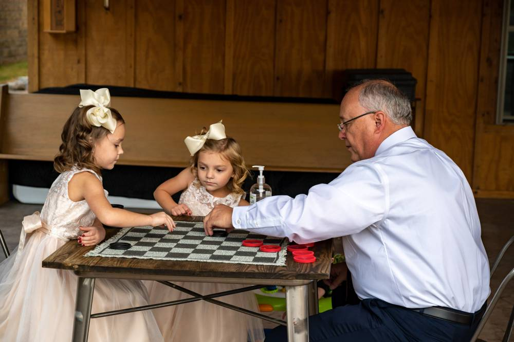 grandfather playing checkers with kids at wedding