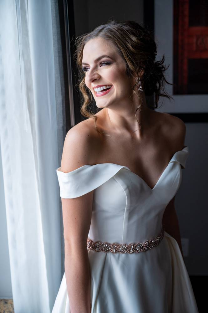 bride laughing in front of window at Mayo Hotel