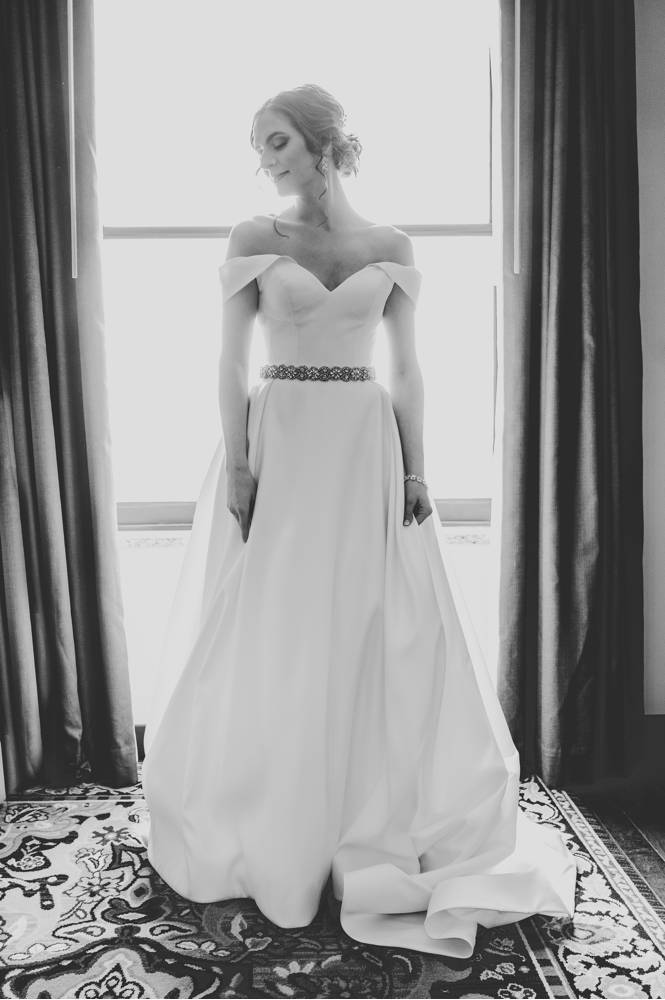 black and white of bride in front of window in Mayo Hotel