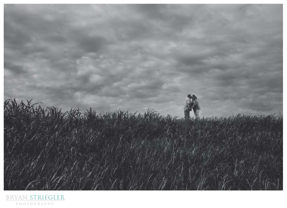 dramatic engagement photo on a hill with clouds