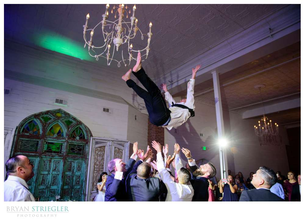groom being tossed into the air