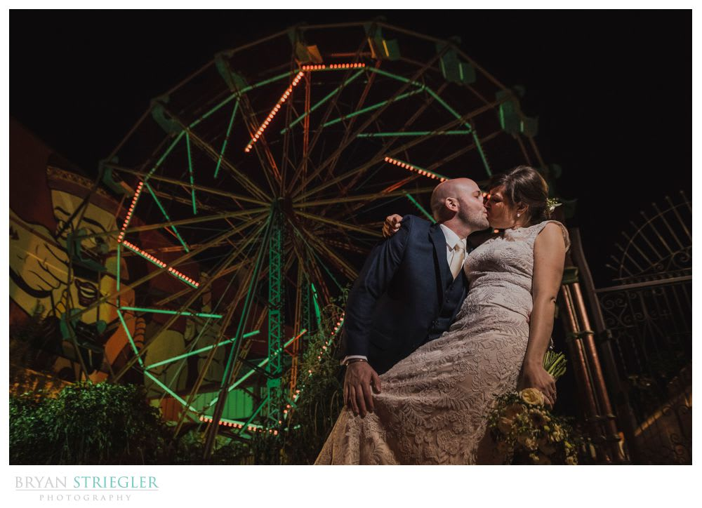 bride and groom in front of ferris wheel in ft. Smith