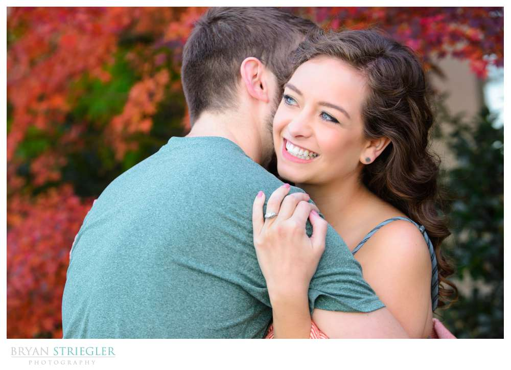 couple hugging and showing engagement ring