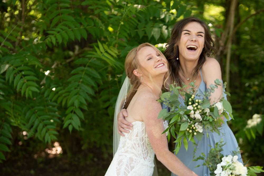 bride and bridesmaid smiling and hugging