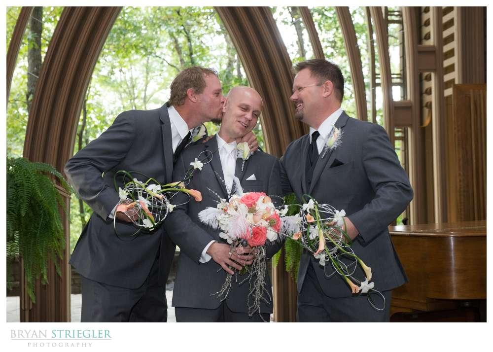 Creative wedding groomsmen kissing groom