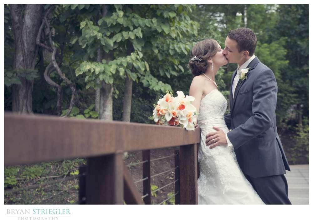 Northwest Arkansas Wedding Photographers kissing on bridge