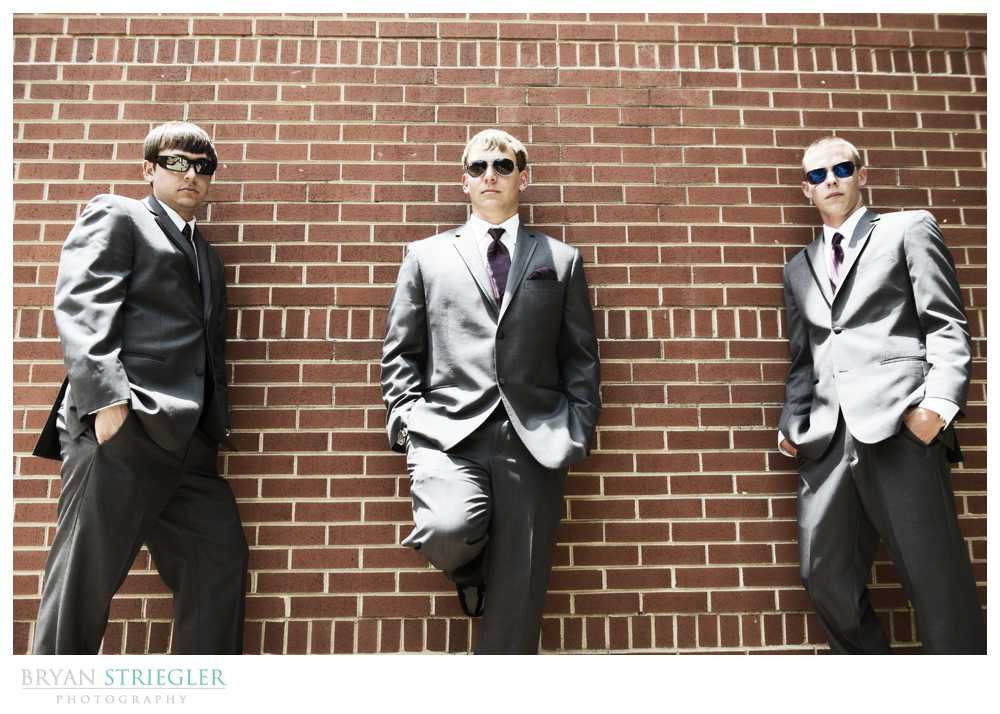 bridal party photos groomsmen leaning on wall sunglasses