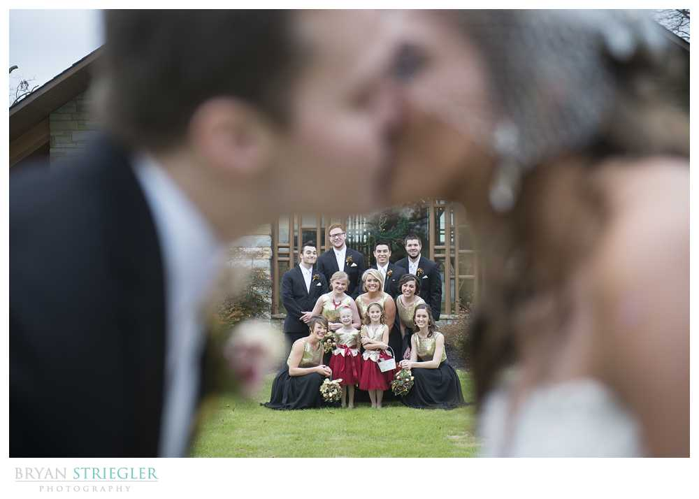 bridal party photos kissing with bridal party in background