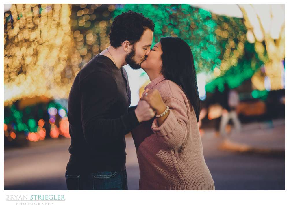 kissing in front of Christmas lights