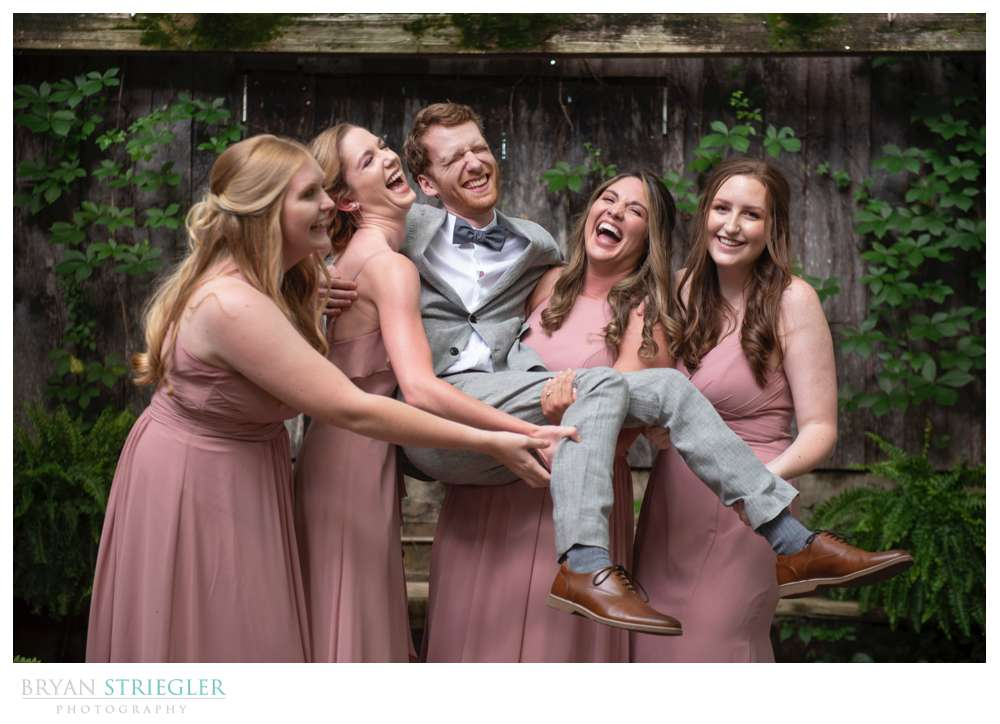 bridesmaids carrying groom