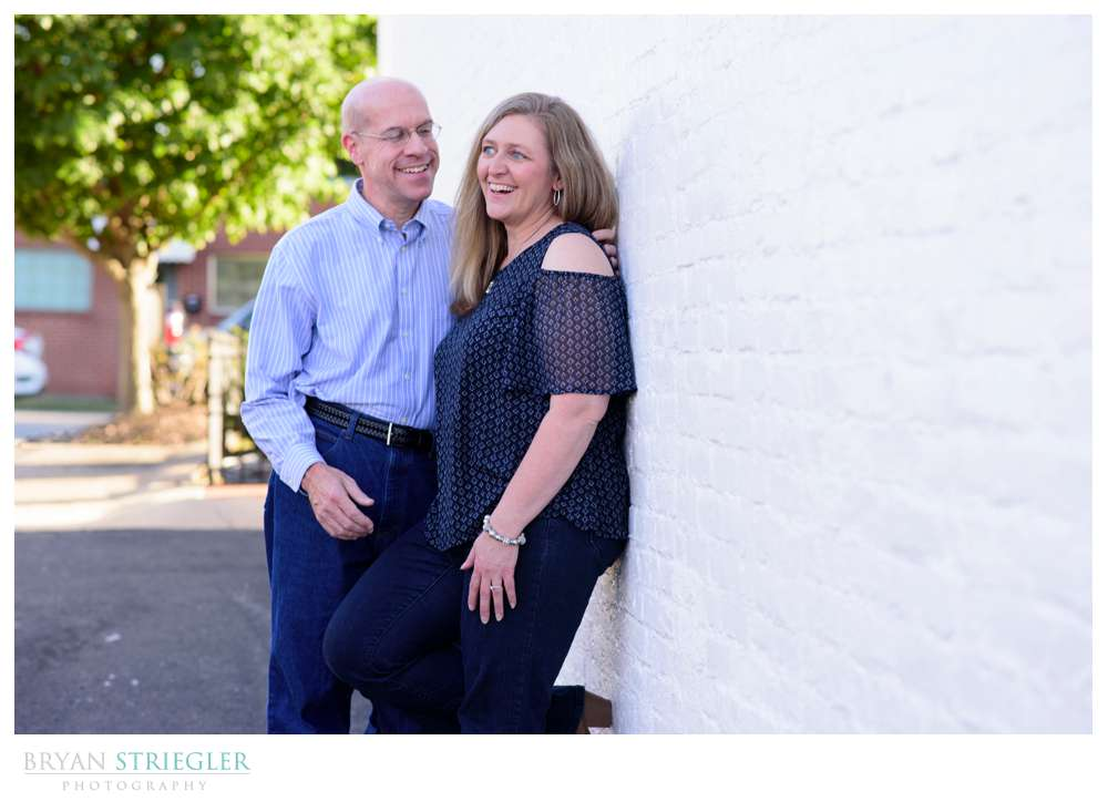 engagement photo leaning against a wall laughing
