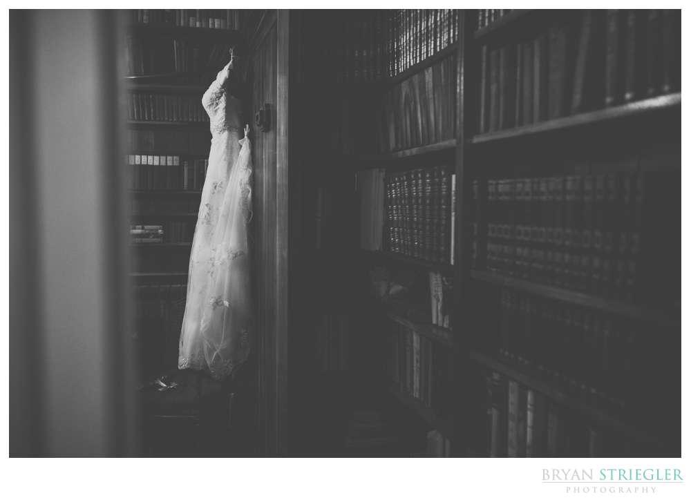 wedding dress hanging up on bookshelf
