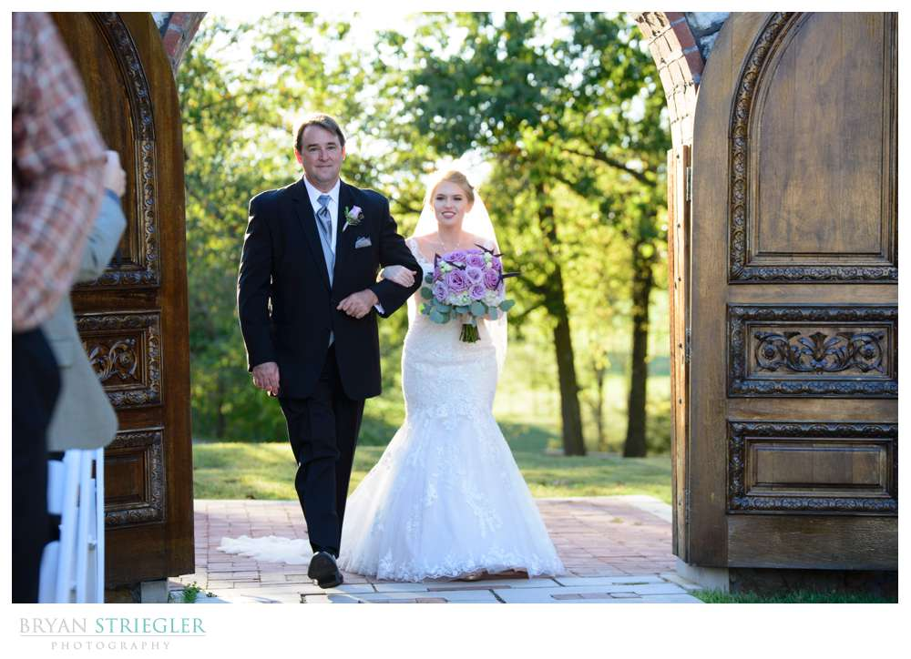Wide shot of bride walking down aisle at Pratt Place Barn