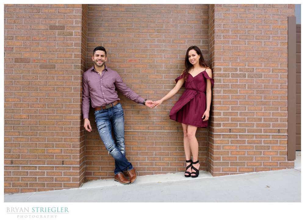 couple leaning against a wall