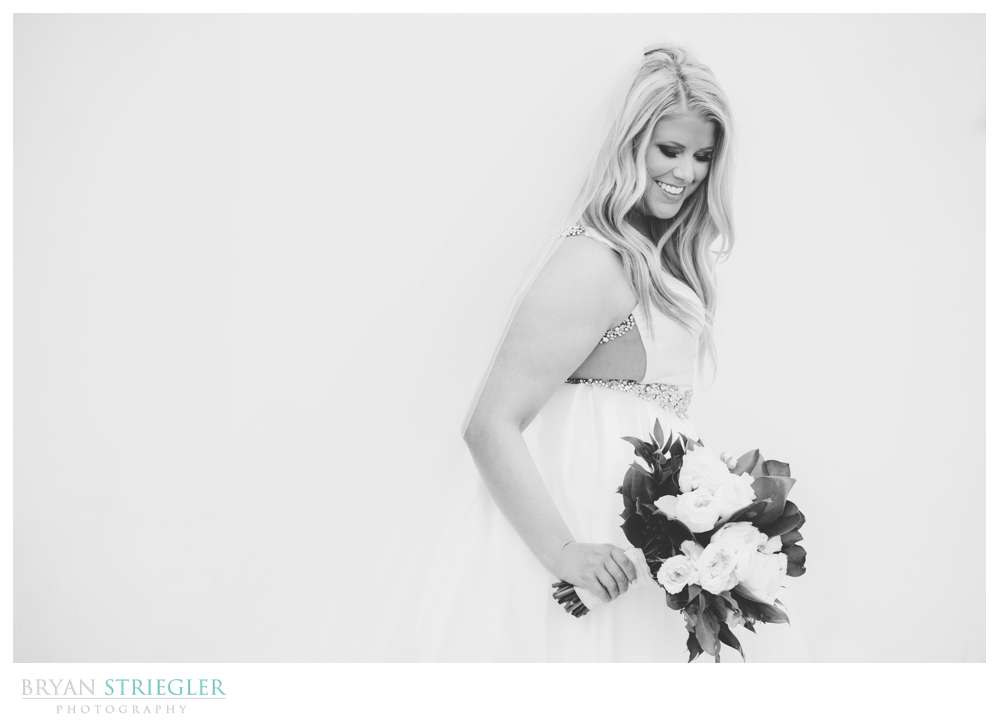 black and white bridal portrait in front of white wall