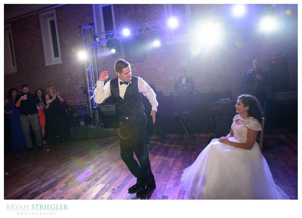 groom dancing for bride before garter
