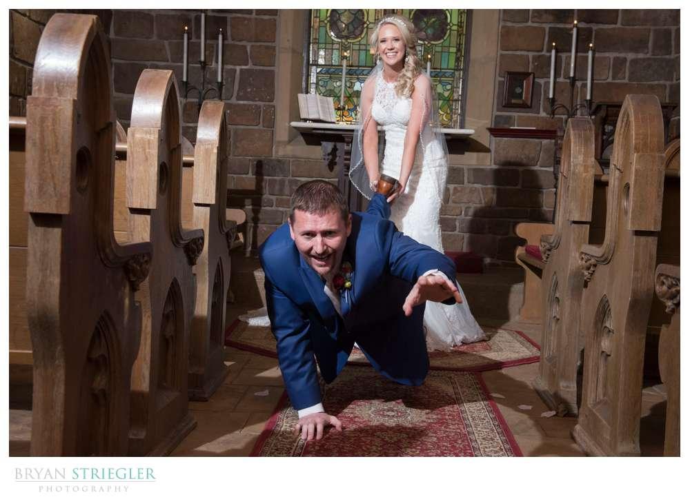 bride holding groom's leg as he crawls away
