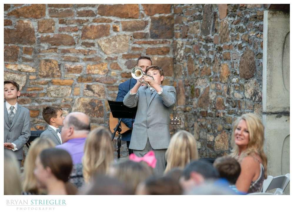 son playing trumpet at wedding