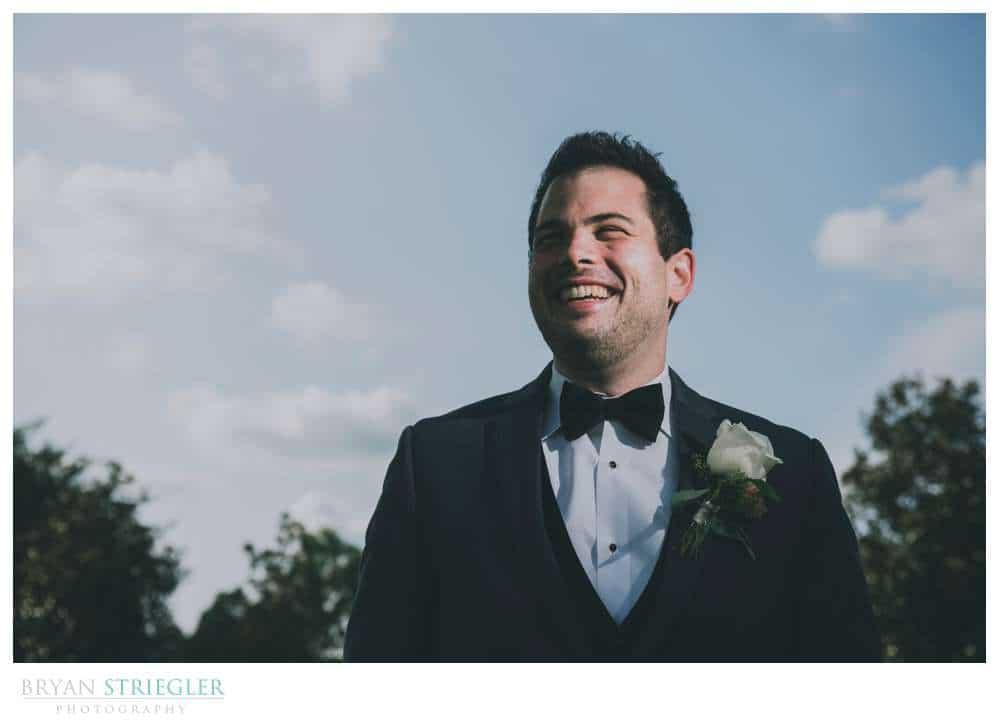 groom portrait with blue sky