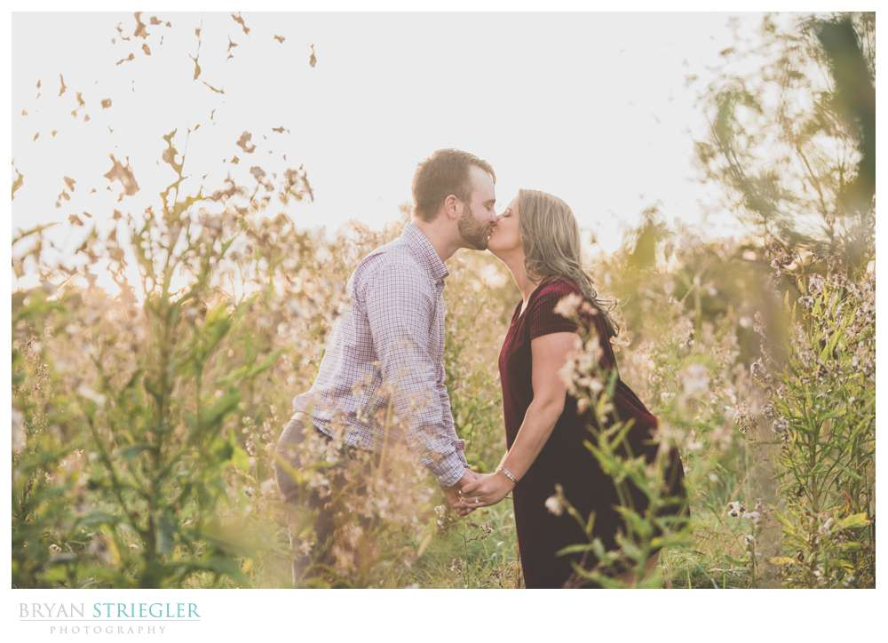 engagement photos kissing in a field