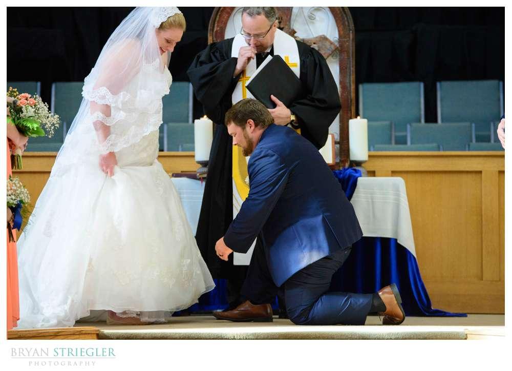 Groom putting on bride's shoe like Cinderella