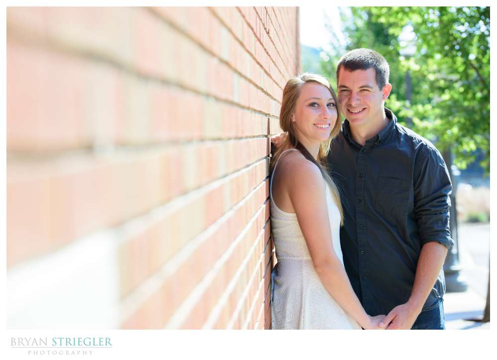 engagement photo leaning against brick wall