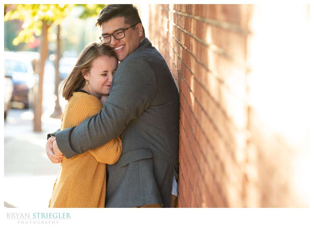 leaning against brick wall engagement photo