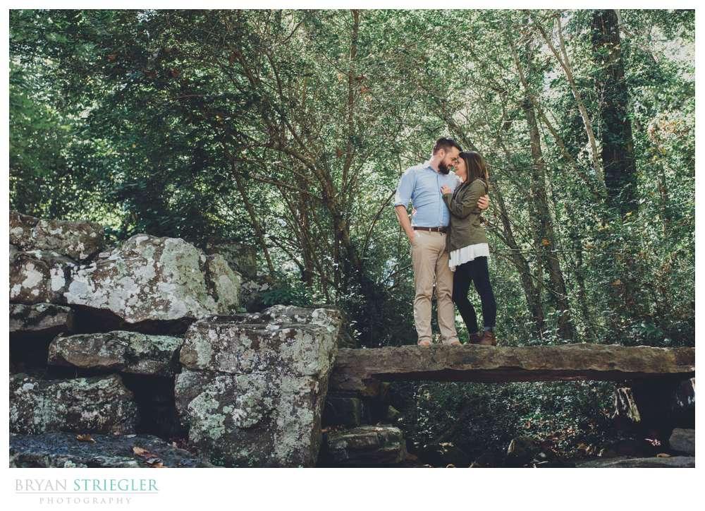 couple standing on rock bridge