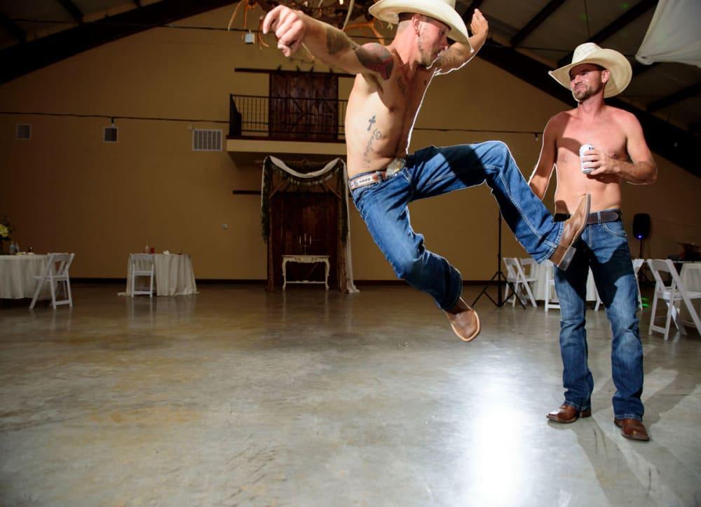 cowboys jumping and dancing at wedding