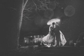 wedding couple in the rain with an umbrella black and white