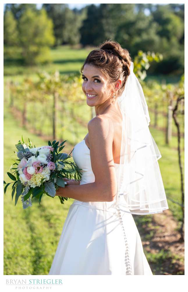 bride in front of grapevines
