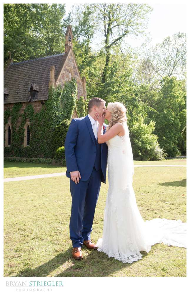 bride and groom kissing in front of St. Catherine's at Bell Gable
