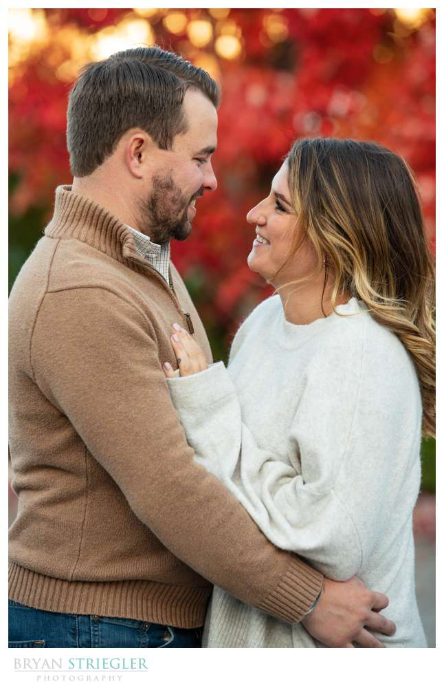 red fall leaves in engagement photo