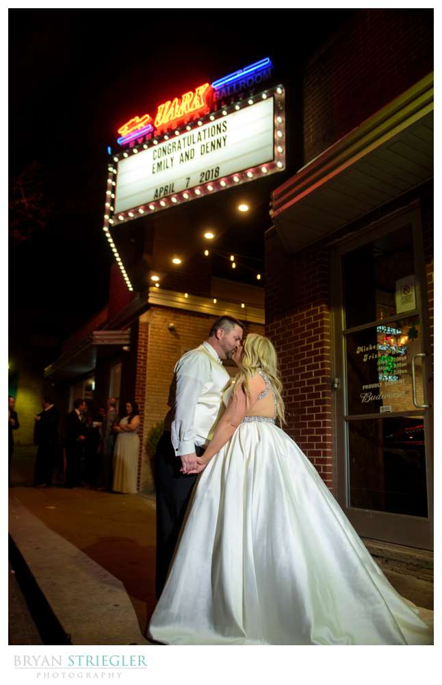 couple kissing in front of Uark bowl